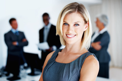 Portrait of confident female executive smiling with colleagues discussing in background
